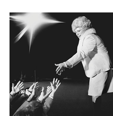 Black and white photo of Mary Kay reaching out into the crowd under a spotlight.