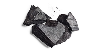 Large fragments of activated charcoal against a white background.