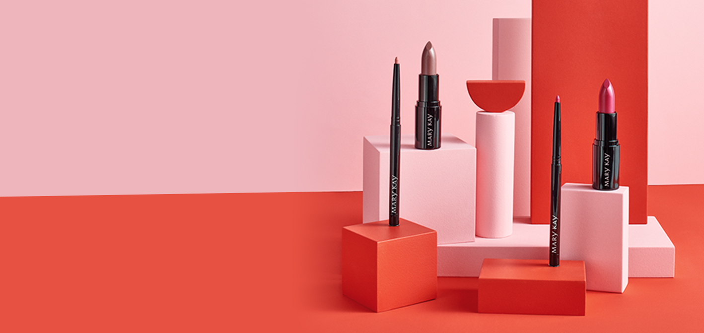 Limited-Edition Mary Kay Lip Kits uncapped and standing on clear blocks against pink and red background.