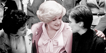 Mary Kay Ash stands between two women with her arms around them and listens as they are talking.