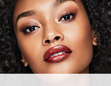 A woman is wearing a Mary Kay ruby-hued makeup artist look featuring the contoured lip trend.