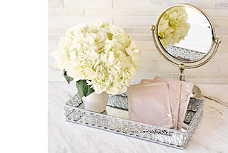 Three packages of TimeWise Repair Lifting Bio-Cellulose Masks are arranged in a silver spa tray next to a vase of white flowers and a mirror.