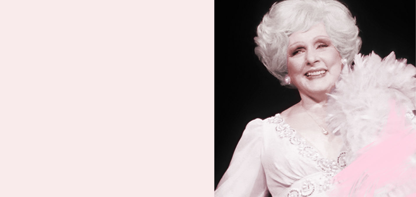 Mary Kay Ash smiles while wearing a gown and feather boa.