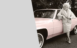 Mary Kay Ash leans against a classic pink Cadillac while wearing a pink fur-trimmed dress suit.