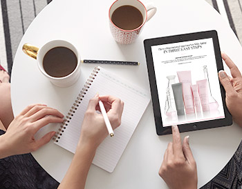 Two women are working at a table with coffee cups, a notebook, and an iPad that shows an image of the new TimeWise Miracle Set 3D from Mary Kay.