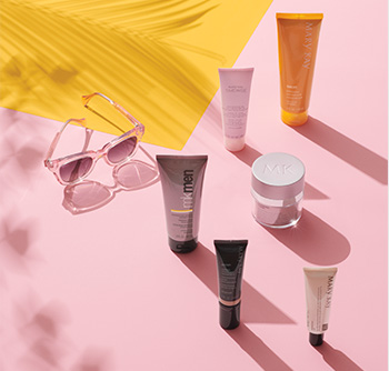 A picture of various Mary Kay skin care products and body care products with SPF sunscreen on a pink and yellow background with sunglasses