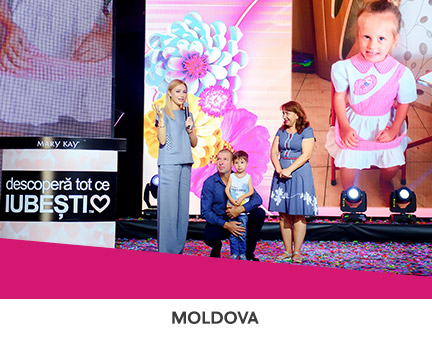 Mary Kay Moldova employees presenting funds on stage to a sick child in support of NGO Save A Life.