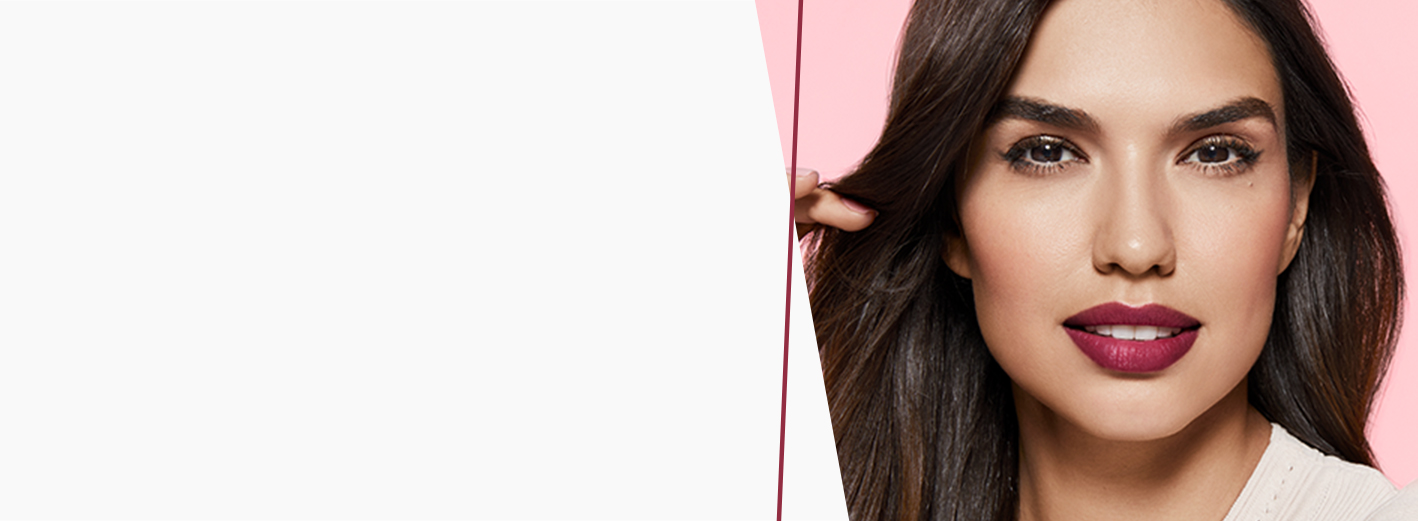 A brunette woman with bold berry lips playing with her hair on a pink background