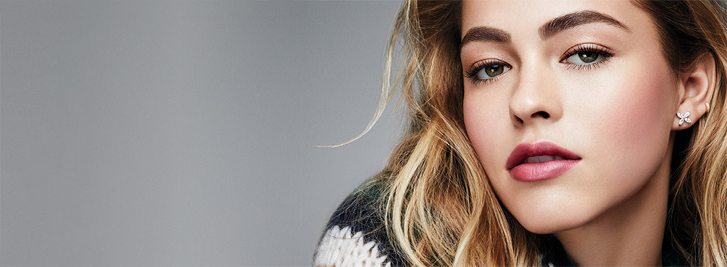 Close-up of model wearing the Glowing Winter Skin makeup artist look from Mary Kay against a gray background.